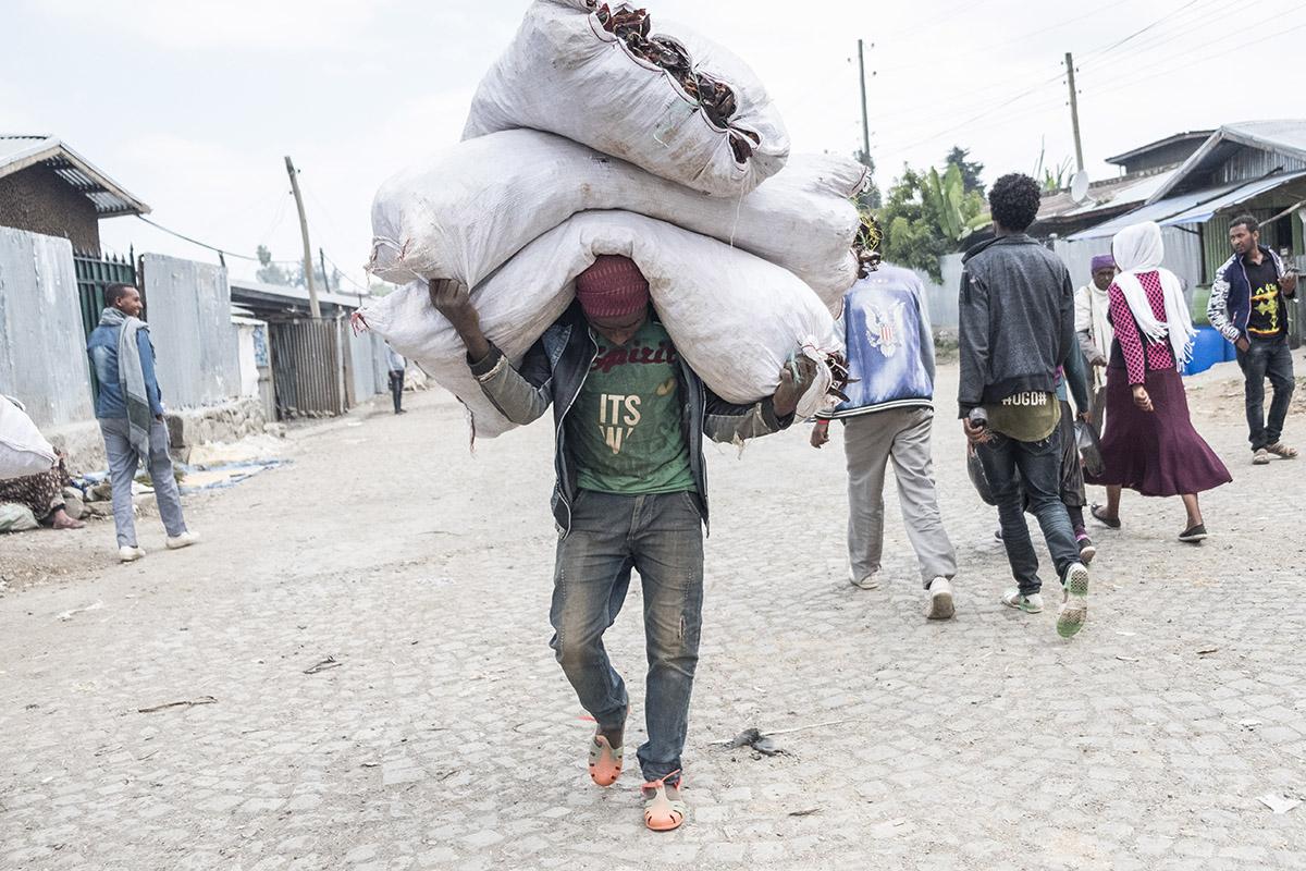 Mann trägt Chilisack   Stiftung Menschen für Menschen
