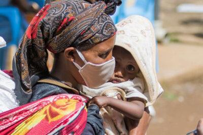 Mutter mit Maske bei Corona-Nothilfeverteilung