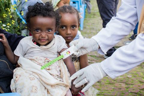 Arm von unterernährtem Mädchen wird gemessen
