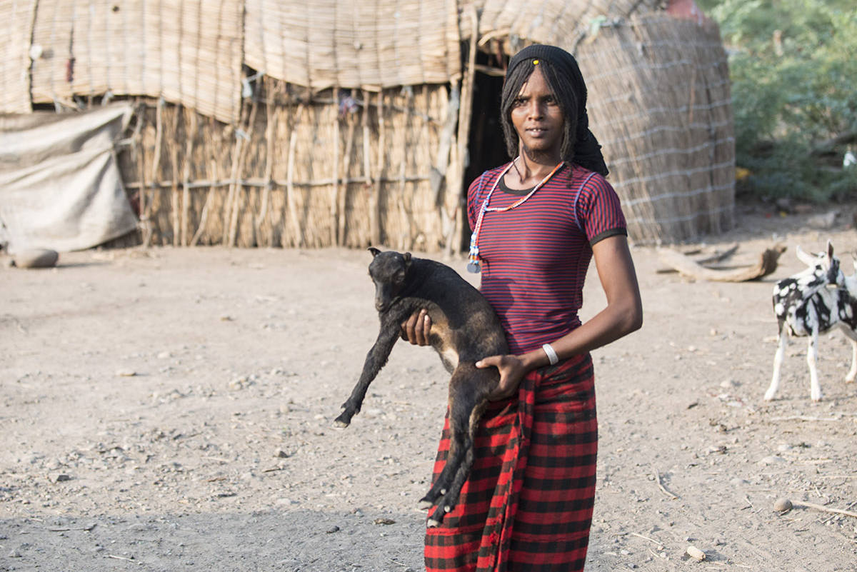 Afar-Hirtin trägt eine junge Ziege