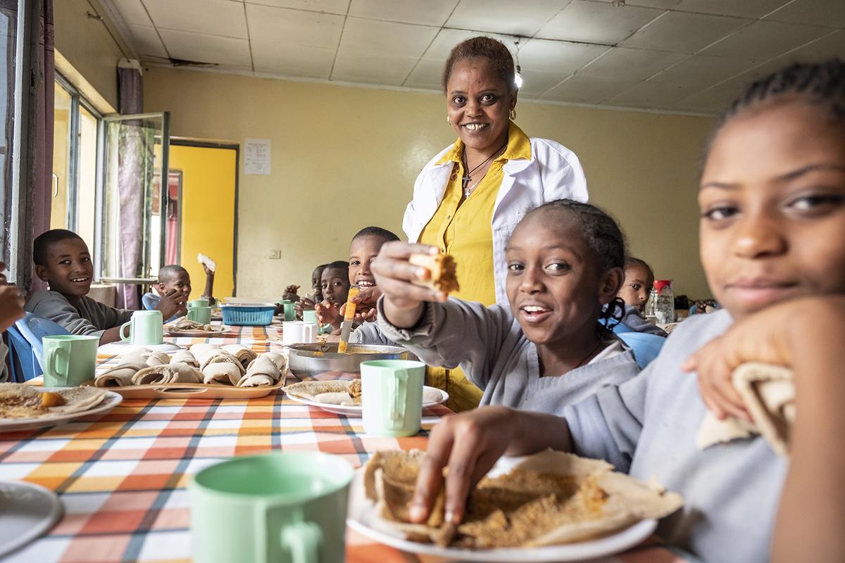 Kinder beim Mittagessen im Speisesaal des Kinderheims