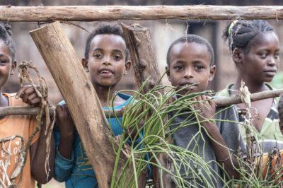 Lachende Kinder hinter Gartenzaun